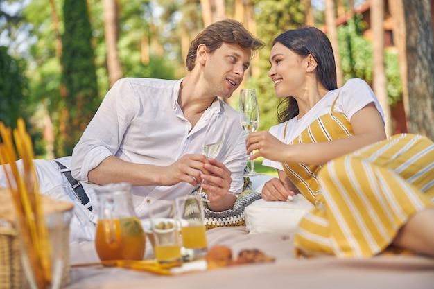 행복 한 미소 젊은 부부는 정원에 앉아 차가운 샴페인을 마시는
