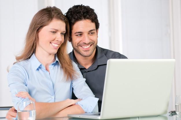 コンピューターのラップトップで一緒に見て幸せな笑顔の若いカップル