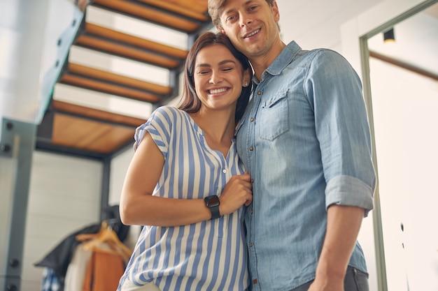 여자가 그녀의 눈을 감고있는 동안 집에 서 캐주얼 옷을 입고 행복 한 미소 젊은 부부