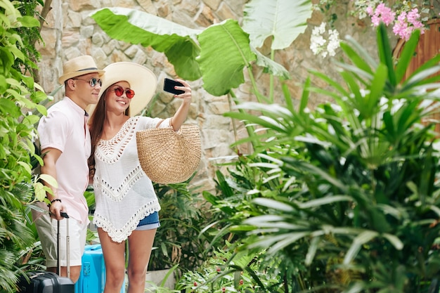 Happy smiling young couple with suitcases taking selfie in garden of luxurious spa resort