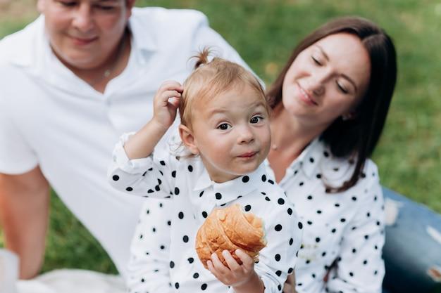 夏の日の公園でのピクニックに幸せな笑顔の若い家族。夏休みのコンセプトです。父の日、母の日、赤ちゃんの日。一緒に時間を過ごす。セレクティブフォーカス