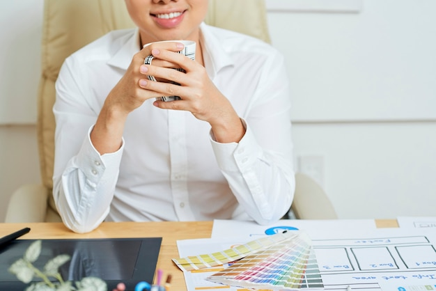 ホームオフィスの机に座って、モルニのマグカップを飲んで幸せな笑顔の若いフリーランスのグラフィックデザイナー...