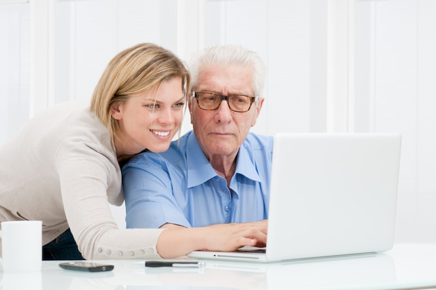 Happy smiling young girl explaining and teaching to her grandparent the use of a modern computer