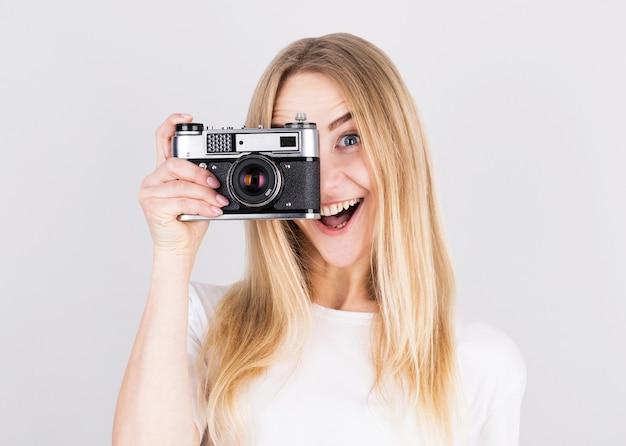 Счастливая улыбающаяся молодая девушка держит камеру и фотографирует
