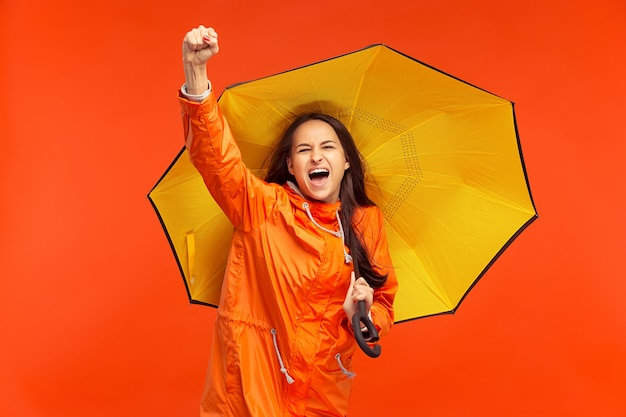 赤で隔離の秋のオレンジ色のジャケットのスタジオでポーズをとって幸せな笑顔の若い女の子。人間の前向きな感情。寒さの概念。女性のファッションの概念