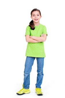 Ragazza sorridente felice con le mani incrociate che guarda l'obbiettivo in piena lunghezza in piedi su sfondo bianco.