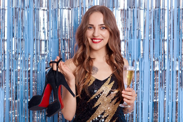 幸せな笑顔の少女と靴とシャンパンのグラスを手に、カメラ目線と幸せそうに見える、青で分離されたポーズ