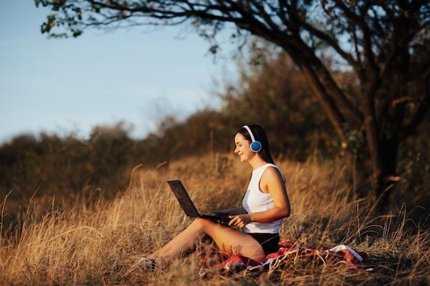 公園でラップトップに取り組んで幸せな笑顔の若い女の子。彼女はラップトップ、フリーランスのビジネスコンセプトに取り組んでいます。