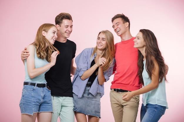 一緒に立って話したり笑ったりする幸せな笑顔の若い友達のグループ親友