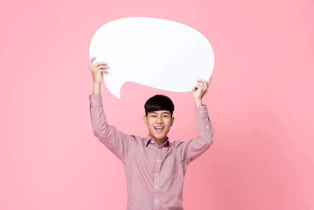 Happy smiling young handsome asian man holding speech bubble