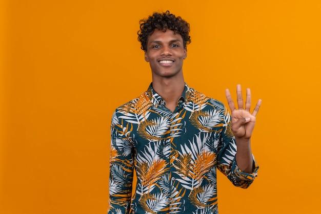 Felice e sorridente giovane uomo dalla carnagione scura bello con i capelli ricci in camicia stampata foglie mentre mostrava con le dita numero quattro