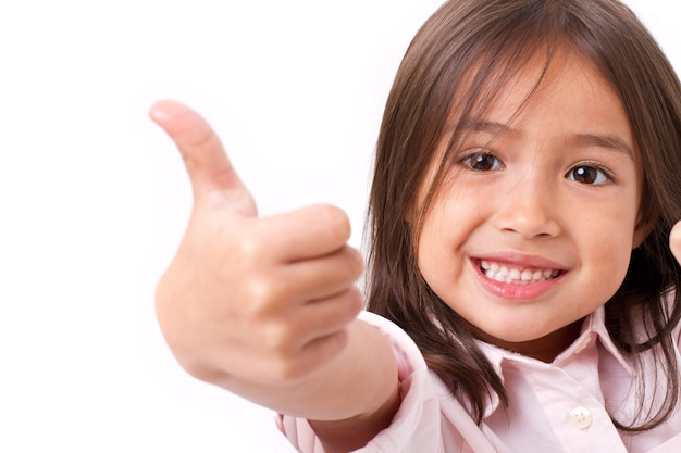 Happy, smiling young little girl giving thumb up gesture, isolated
