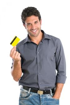 白い背景で隔離のクレジットカードを保持している幸せな笑顔若い男