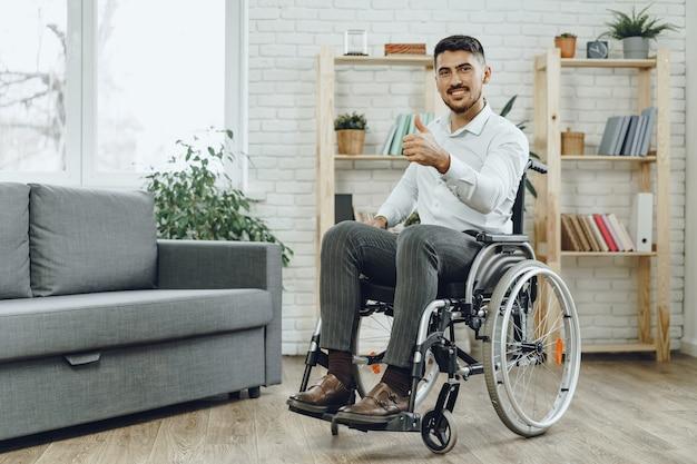 家にいる車椅子の幸せな笑顔の若い男