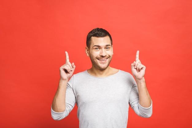 幸せな笑顔の若い男が提示し、見せています