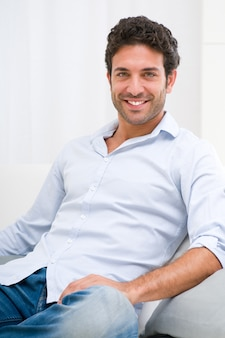 Happy smiling young man relaxing on sofa at home