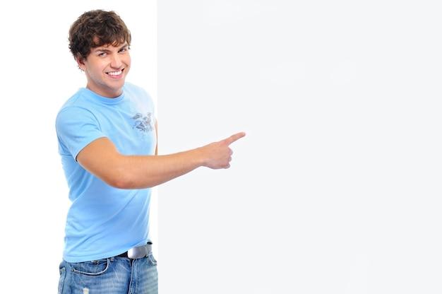 Giovane sorridente felice che mostra dal dito sulla bandiera vuota bianca