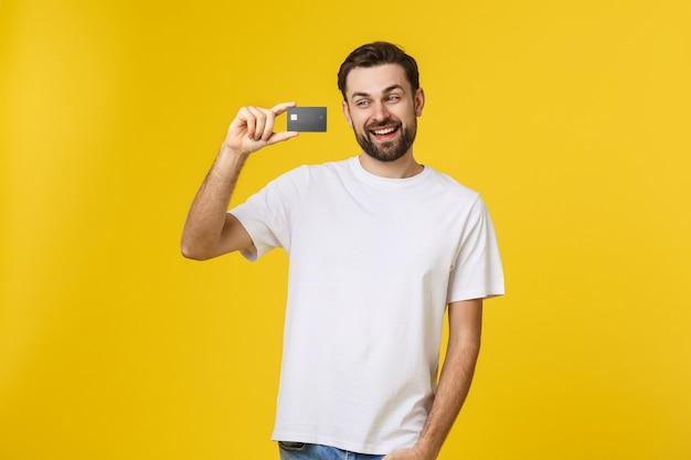 Счастливый улыбающийся молодой человек показывает кредитную карту, изолированную на желтом пространстве