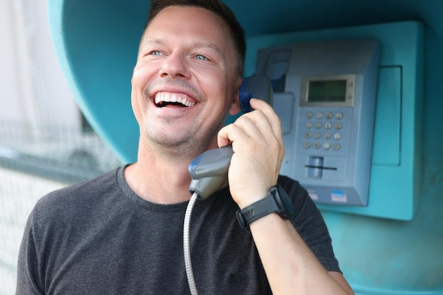 Happy smiling young man talking on phone in booth city telephone communication concept