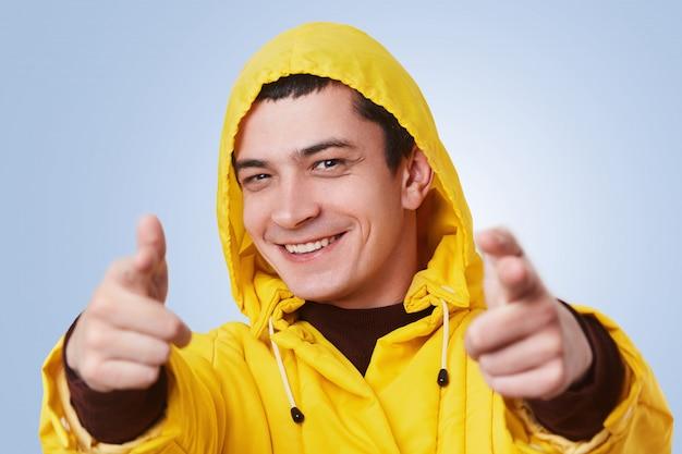 Счастливый улыбающийся молодой человек носит желтый анорак и капюшон, указывает на вас с радостным выражением лица, выбирает кого-то, изолированных на синем