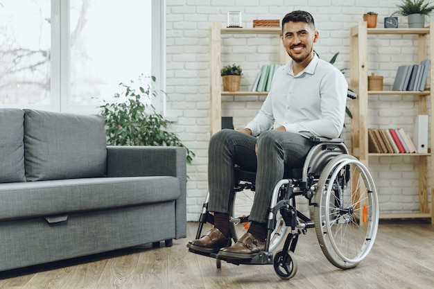 Happy smiling young man in a wheelchair staying at home