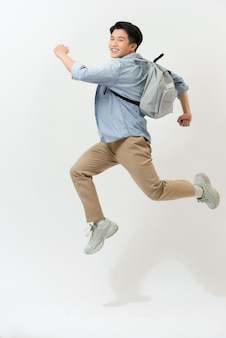 Happy smiling young man with backpack jumping in air over white background
