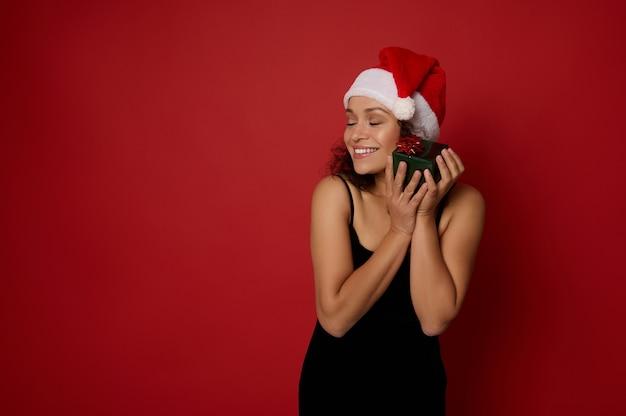 검은색 이브닝 드레스와 산타 모자를 쓴 행복한 미소 짓는 젊은 혼혈 여성, 크리스마스 선물 상자를 부드럽게 껴안고 뺨에 대고 광고 복사 공간이 있는 빨간색 배경에 눈을 감고 포즈를 취합니다.