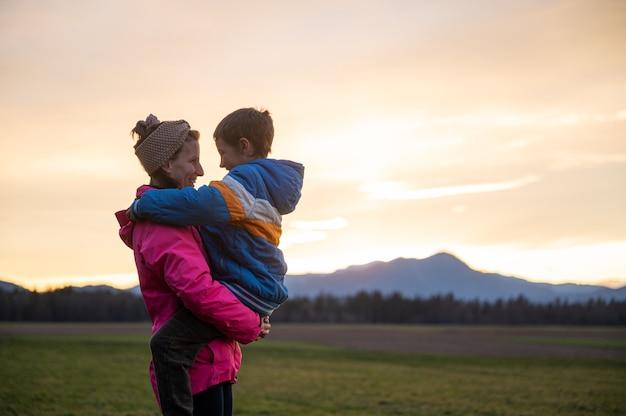 彼らが夕方の空の下で美しい牧草地の外に立っているときに愛情を込めて彼を見ている息子を腕に抱いて幸せな笑顔の若い母親。