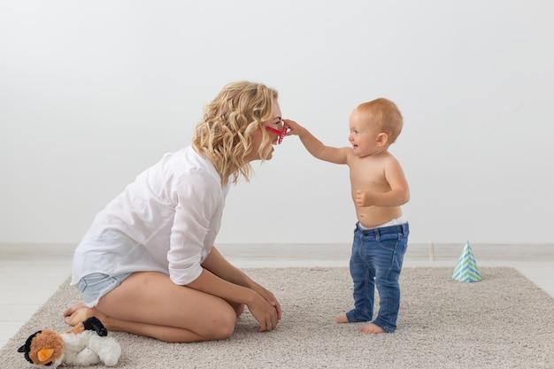 집에서 작은 아기와 함께 노는 행복 한 웃는 젊은 어머니