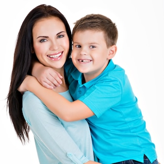 Happy smiling young mother with son. isolated on white