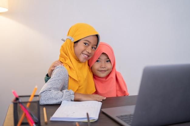 一緒にカメラを見てラップトップと幸せな笑顔の若いイスラム教徒の子供