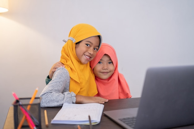 Happy smiling young muslim kid with laptop together looking at camera