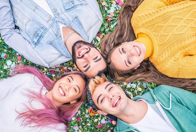 公園の芝生の上に横たわって空を見ながら自分撮りをしている幸せな笑顔の若者-屋外で一緒に楽しんでいる若い学生との幸せな友情の概念