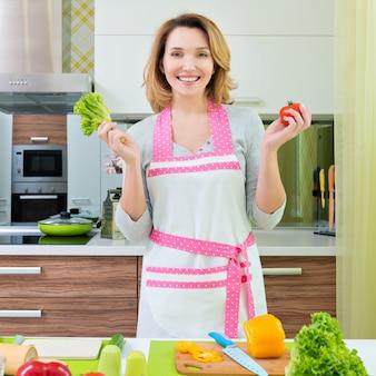 幸せな笑顔の若い女性がキッチンでサラダを調理します。