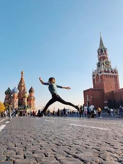 赤の広場でジャンプする幸せな笑顔の若い女性の全身の肖像画