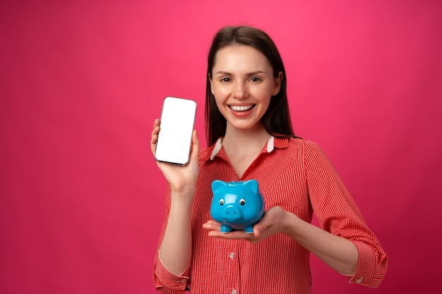 분홍색 배경에 파란색 돼지 저금통을 들고 행복한 웃는 젊은 여성