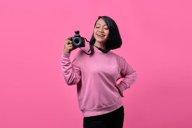 ピンクの背景にカメラを保持している幸せな笑顔の若い女性