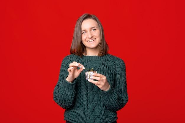 빨간색 격리 된 스튜디오 배경 위에 작은 선물 상자를 들고 행복 한 미소 젊은 여자