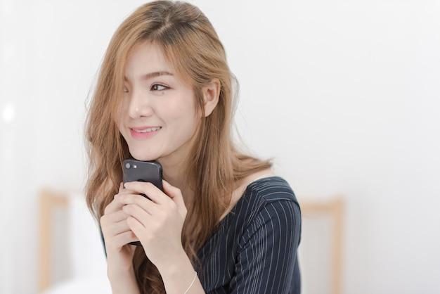 幸せな笑顔の若い女性は彼女の携帯電話を保持します