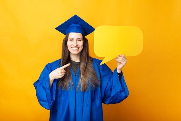 Счастливая улыбающаяся молодая женщина в синем халате, указывая на пустой желтый речевой пузырь