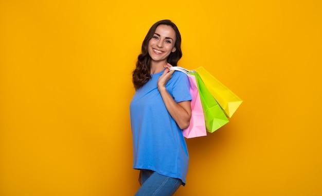 カラフルな買い物袋とカジュアルな服を着て幸せな笑顔の若い女性は黄色の背景にポーズをとっています
