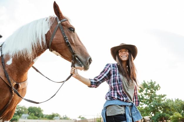 農場で散歩に彼女の馬を取るカウボーイハットで幸せな笑顔の若い女性