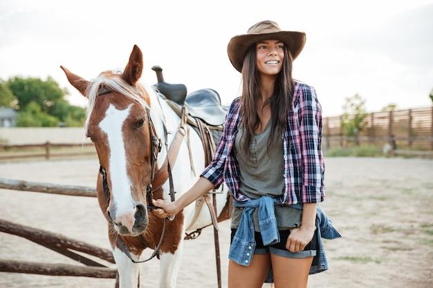 農場で彼女の馬とカウボーイハットで幸せな笑顔の若い女性