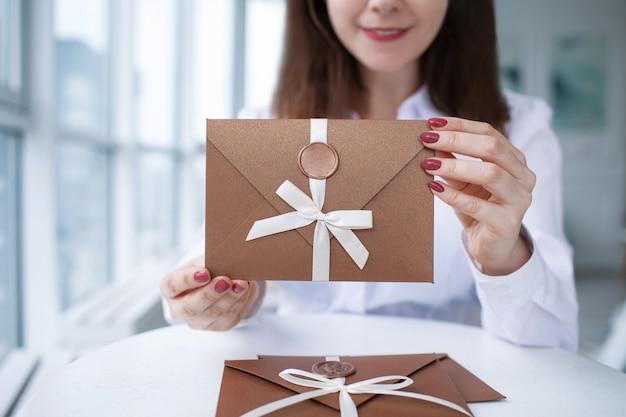 白いカジュアルな服装で幸せな笑顔の若い女性は商品券を保持します。ギフト券、ギフト券または割引のクローズアップ。