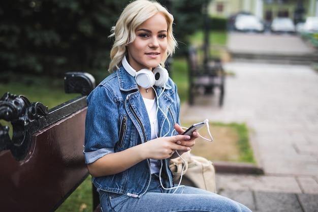 Счастливая улыбающаяся молодая женщина, слушающая музыку в наушниках и использующая смартфон, сидя на скамейке в городе