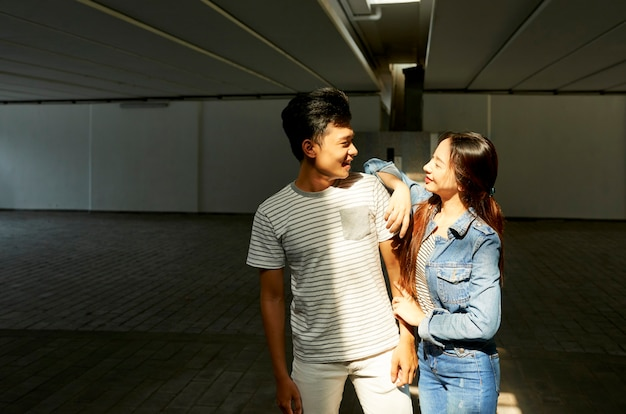 日差しの中で立っている彼氏を見て幸せな笑顔の若い女性