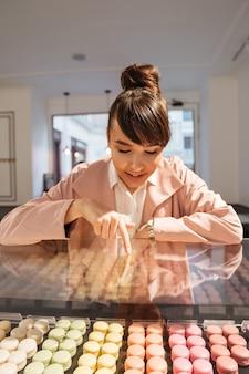 Giovane donna sorridente felice che esamina le pasticcerie attraverso la vetrina di vetro