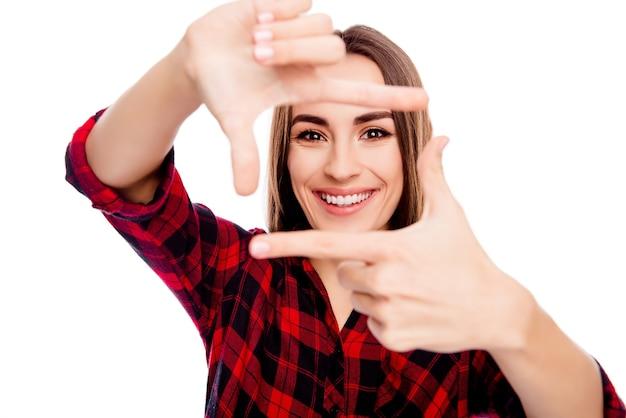 손가락으로 프레임을 만드는 행복 한 웃는 젊은 여자