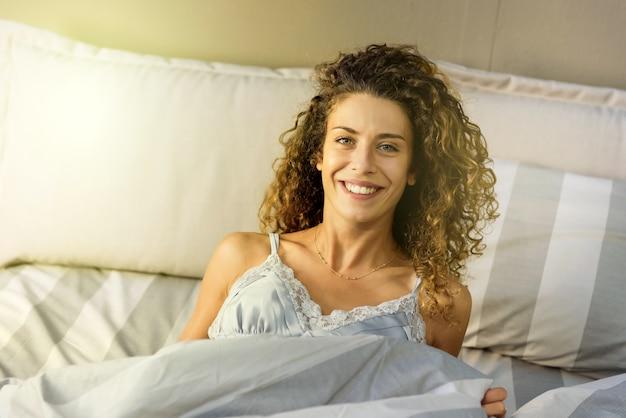 정면 초상화 가까이에 건강과 웰빙 개념에 상쾌한 수면 후 그녀의 침대에서 편안한 행복 웃는 젊은 여자