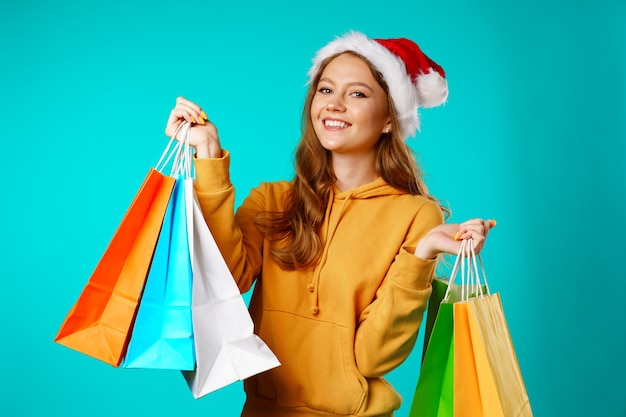 Happy smiling young woman in santa hat holding shopping bags